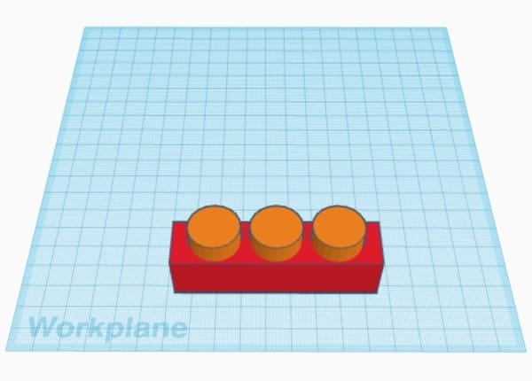 Red rectangle with three orange cylinders on the Tinkercad workplane