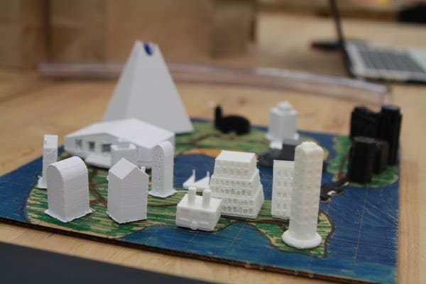 3D prints sitting on cardboard colored to look like an island