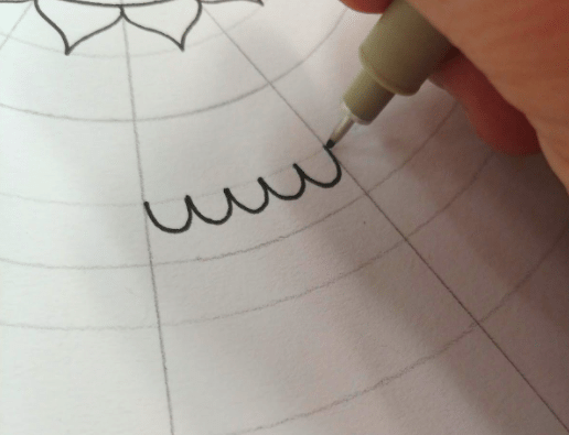 A pen being used to fill in the lines between the circles