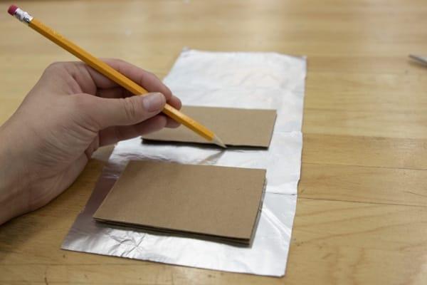 Pencil tracing around cardboard rectangles onto aluminum foil.