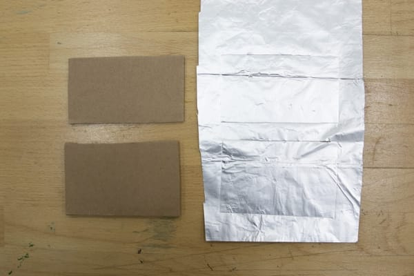 Cardboard rectangles next to aluminum with pencil trace outline.