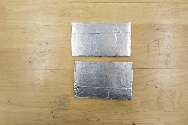 Two rectangles: aluminum foil glued onto the top of the cardboard rectangle cutouts.