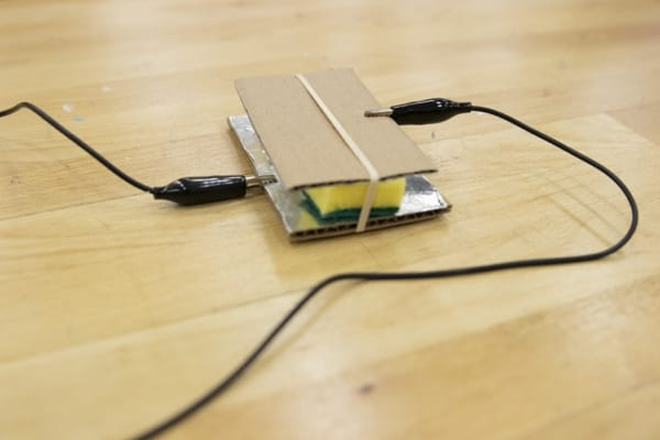 Closeup of the circuit switch with an alligator clip attached to the aluminum foil and another alligator clip attached to the top piece of cardboard.