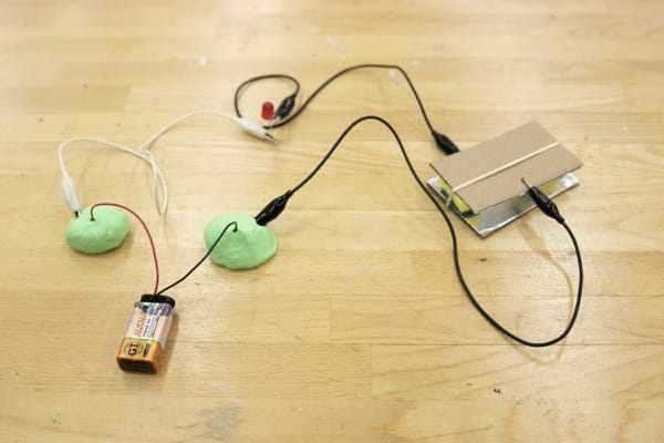 Battery connected to Play Doh sitting next to the circuit switch, connected to the Play Doh with an alligator clip.