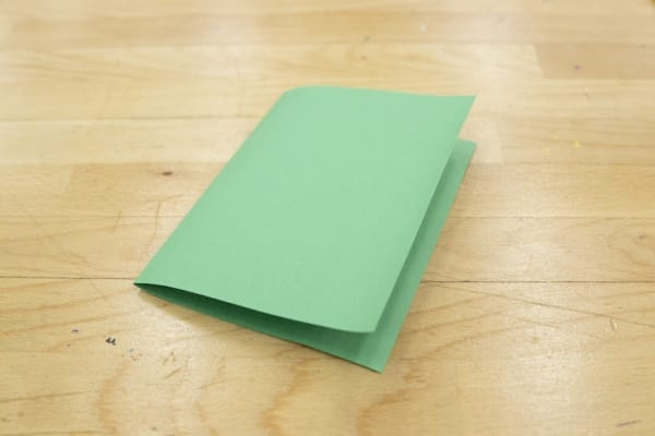 Green construction paper folded in half vertically.