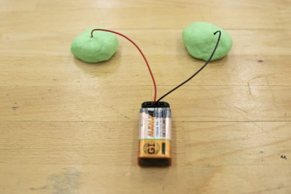 Red (positive) and black (negative) wires from the battery connected to two mounds of Play-Doh.