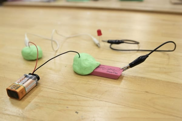 Battery connected to the Play-Doh and an alligator clip connected to a rubber eraser.
